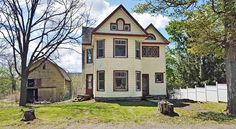 This small-town farmhouse features attractive details including stained glass, arched windows, and a lofty barn, and is in need of a new roof and systems along with some TLC.