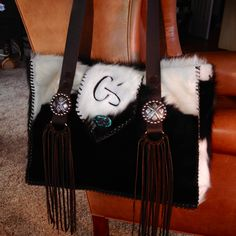 A custom Cowhide Diaper Bag from gowestdesigns.us. This one features the customers brand and her own card suit conchos.