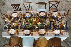 this table setting is fabulous. the use of deep blue paired with gold gives a very regal and elegant vibe.