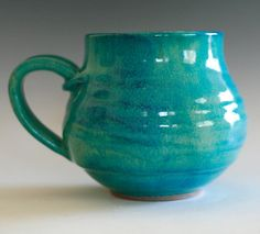 "large porcelain coffee mug. 4"" tall, 3"" opening, holds 18 oz. This mug is wheel thrown and high fired. Glazed in turquoise."