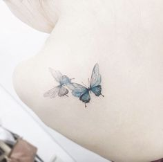 Playful butterfly tattoos on back shoulder by Tattooist Flower