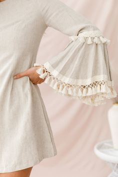 Buy the Sahara Tassel Trim Bell Sleeve Dress Beige only at Selfie Leslie! Kurta Designs Women, Kurti Neck Designs, Dress Neck Designs, Sleeve Designs, Blouse Designs, Stylish Dress Book, Stylish Dresses For Girls, Dress Clothes For Women, Stylish Kurtis Design