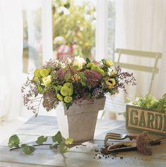 En una maceta  Un ramo de flores puede quedar precioso en una maceta que ya no uses. Este centro se ha configurado con crisantemos, jacintos...