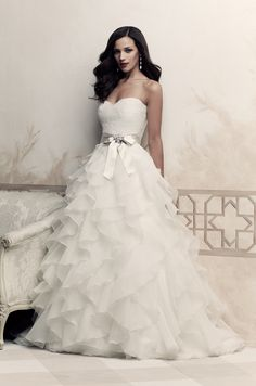 French Alençon Lace and Organdy Wedding Dress. Strapless sweetheart lace bodice with ribbon and brooch at natural waist. Ruffled organdy skirt. Sweep train.