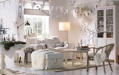 Valkoinen olohuone, jossa riippuvia ja luonnosta kerättyjä koristeita.