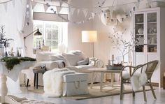 A white living room decorated with hanging ornaments and winter themed natural elements.