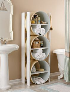 Here, large cylinders with shelves make a modern sculptural storage unit. Rolled towels sit comfortably in the curved base