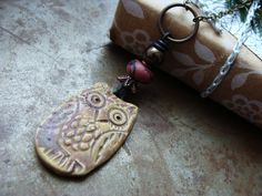 """Wear this woodsy owl as a whimsical reminder what a clever girl you are! The artisan ceramic owl in a warm brown glaze is paired up with a polymer clay disk in copper and a branch design and a tiny ceramic bead in metallic bronze. The brass chain measures 29"""" long. The pendant measures 3"""" long."""