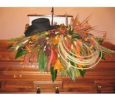 Cowboy's hat and lariat in casket spray with wheat, antlers and pheasant feathers.