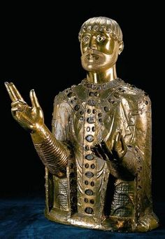 Bust Reliquary of St. Baudime, c. 1180-1200; Romanesque (French, Auvergne); gilded bronze, gems and enamel with a wood core; Parish Church of Saint-Nectaire, Puy-le-Dôme. This nearly life-sized bust is one of the earliest surviving objects of its kind and travels outside of France for the first time. The stippling of the beard, the rhythmic curls of hair and the elegant patterning of the saint's vestments conjure a human presence even as its gold surfaces assert the holy nature of the…