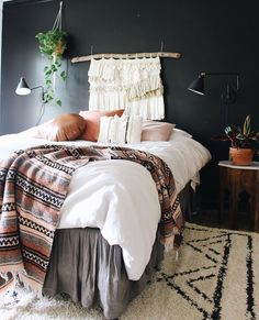 Bohemian style bedroom | Boho decor in bedroom includes Aztec throw blanket, Black and white design rug, white comforter, soft pallet throw pillows, macrame wall hanging and plants. Just gorgeous!