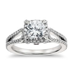 Undeniably striking, this platinum engagement ring showcases a dramatic depth of pavé-set diamonds arranged in a halo and split shank design.