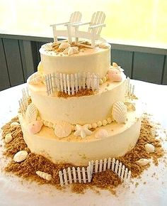 Three Tier Beach-Inspired Cake with Seashells, White Picket Fencing, and an Adirondack Chair Cake Topper