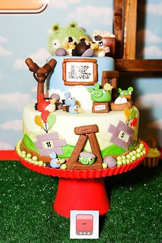 A two-tiered cake with molded chocolate and fondant scenery features 3D fondant birds and game elements by Lynlee's Petite Cakes. Source: Banner Events
