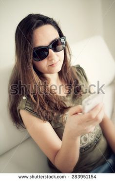Woman with sunglasses looking smartphone on the sofa.