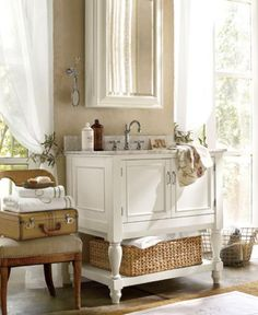 A beautifully crafted vanity brings big style to this small bath. The piece has turned legs and framed doors that evoke European farmhouse furniture. A chair placed beside it creates a convenient spot for dressing – or to stack towels for overnight guests.  Benjamin Moore™ Paint Color:  955 berber white