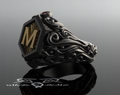 Baroque Rampart Distinction and gravity.  Flamboyant, yes-but also powerful and uncompromising. This intoxicating and intricate gents monogram ring makes no apologies for its unabashed decadence. A bold single initial is raised up from a layered radial starburst engraving, crafted from solid 18kt European gold. Set in a heavyweight hexagonal frame with a subtle coin edge for some unflinching masculine boldness. Set off in the North-South compass points are a pair of dark blood red color treat...