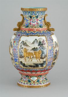 """FAMILLE ROSE PORCELAIN VASE In baluster form. With bat-form handles and relief decoration of deer, horses, water buffalo, and goats on a blue lattice ground. Six-character Qianlong mark on base. Height 17.5"""" (44.4 cm)."""