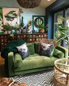 This is insane, but really cool! Botanical dark boho living room dreams with a forest green velvet couch! Love it!