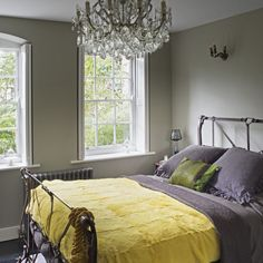 Plush fabrics, an iron bedstead and an ornate chandelier give this bedroom a luxurious feel. Switching curtains to shutters also makes the room feel bigger and brighter