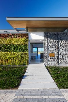 gabion blocks filled with stone, one side planted with a living wall green - fence inspiration