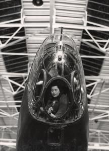 A Second World War woman assembly worker (working for the London Aircraft Production Group) sits in the glass nose-cone section of a Handley-Page Halifax bomber at Leavesden Works.    Unknown photographer, 1941-1945