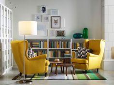 イエローのウィングチェア2脚、ウォールナット材突き板のネストテーブル、ホワイトのオープンな書棚、ガラス扉付き書棚を置いた明るいリビングルーム。