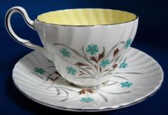 This is a pretty mid century Foley, E. Brain, England brown, aqua and brown floral cup and saucer with a sunny yellow cup interior and platinum trim made in the 1950s. The pretty swirl molded bone china cup is 2.65 inches high, the saucer is 5.5 in diameter. Both pieces are in very good +++ used vintage condition with