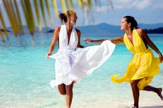 two women running on the shore wearing beach wedding dresses in paradise