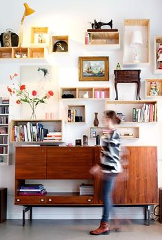 In this salon hang, wooden boxes filled with decor items and books mingle with art to create a wall of personality. Unexpected objects such as a vintage sewing machine, framed lampshade and antique side table create a sense of surprise and interest. Photography by Anke Leunisse and Kim de Groot, via Bloesem.