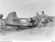 WESTERN DESERT, EGYPT. 1942-08-14. THIS GERMAN MESSERSCHMITT BF109F PLANE MADE A FORCED LANDING ON THE MAIN BITUMEN ROAD NEAR EL ALAMEIN STATION WHEN VITALLY HIT BY ANTI-AIRCRAFT FIRE. ANOTHER ...