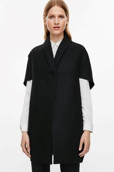 This cape is made from a wool mix with a felt finish. Designed with a modern…