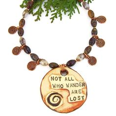 """The """"Not All Who Wander are Lost"""" handmade necklace features ana artisan ceramic pendant with the saying and a spiral, brown agate gemstones and copper spirals - one of a kind jewelry. -- By Shadow Dog Designs Jewelry"""
