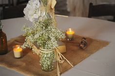 Burlap, baby's breath, mason jars, hydrangeas and vintage bottles discovered in the woods