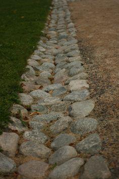 Ränndal mellan grusväg och gräsmatta minskar erosion. Gunnebo slott.