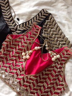 Beautiful lengha and saree blouse details from Kuvira London. Hot pink and black and gold cut work embroidery www.kuviralondon.com