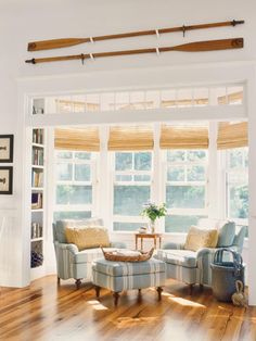 Love the oars! So light and bright! Maine house. Lake house decor, lake cottage, coastal, matchstick blinds, blue striped slipcovers, wood floor...