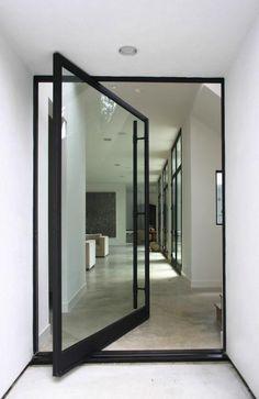 Porta pivotante de vidro com puxador no comprimento inteiro da porta, a deixa muito mais moderna. Fotografia: http://www.decorfacil.com/portas-pivotantes/
