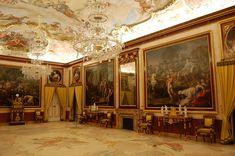 Palacio Real de Aranjuez. Los apartamentos de la Reina y del Rey están separados hoy por el Salón de Baile, situado en el centro de la fachada sobre el Parterre, en el eje del Palacio. Su ambiente responde al siglo XIX, presidido por los retratos de Alfonso XII y Alfonso XIII, pintados por Ojeda y Garnelo, respectivamente.