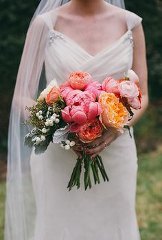 Brides.com: . A mixed bouquet of bright-and-pale pink peonies and ranunculus, combined with coral garden roses and white berries, created by Georgia-based florist Virtu Floral and Event Design.