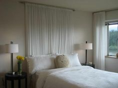 Bett mit weißen Gardinen für eine zärtliche Atmosphäre