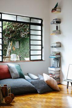 Sala de estar tem parede galeria com quadros e objetos de afeto.