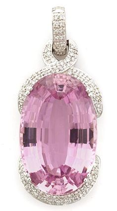 A kunzite and diamond pendant/enhancer oval-shaped kunzite measuring approximately: 31.4 x 20.9 x 12.9mm; mounted in eighteen karat white gold