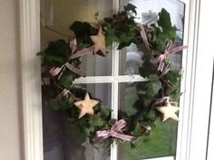 Homemade xmas wreath . Used only ivy and wound it around itself. I added wooden stars taken from a xmas tree garland and made little ribbon bows, attached with craft wire.