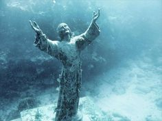 Underwater Jesus Christ on Ocean Floor Reaching with arms lifted to the heavens at John Pennekamp Coral Reef State Park