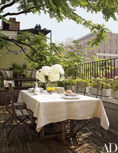 One of the apartment's three terraces is outfitted with French café chairs for dining.