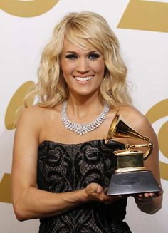 Carrie Underwood poses with her award for Best Country Solo Performance backstage at the 55th annual Grammy Awards in Los Angeles, California February 10, 2013.