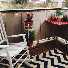 Loving how our apartment patio is coming along! Blue and cream chevron rug, ferns, gardenias, cafe lights and a pop of red!   My own little oasis!