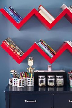 Bold blue boys room with red accents! Bright red zig zag bookshelves against blue wall. Well organized blue desk with fun storage.