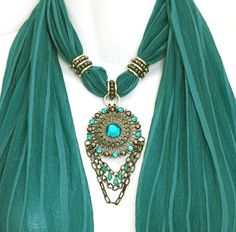 """A mid shade of teal combines beautifully with the steel grey pendant and teal glass jewels. The matching scarf rings are hand-made from hematite beads for a perfect match. Chains at the bottom of the pendant add movement and further interest. The scarf has matching fringe on the ends. The overall effect is very pretty and just a little bit exotic.    Jewellery scarves ! I enjoy designing them, and LOVE wearing them. They transform even the blandest outfit from *yawn* to """"ooh-la-lah !"""". I…"""